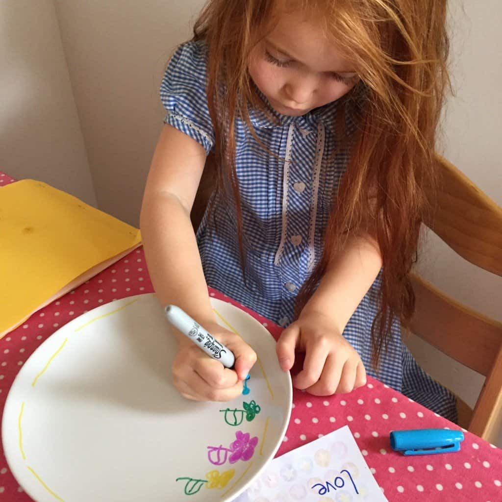Ava decorating a plate with Sharpie pens for Father's Day
