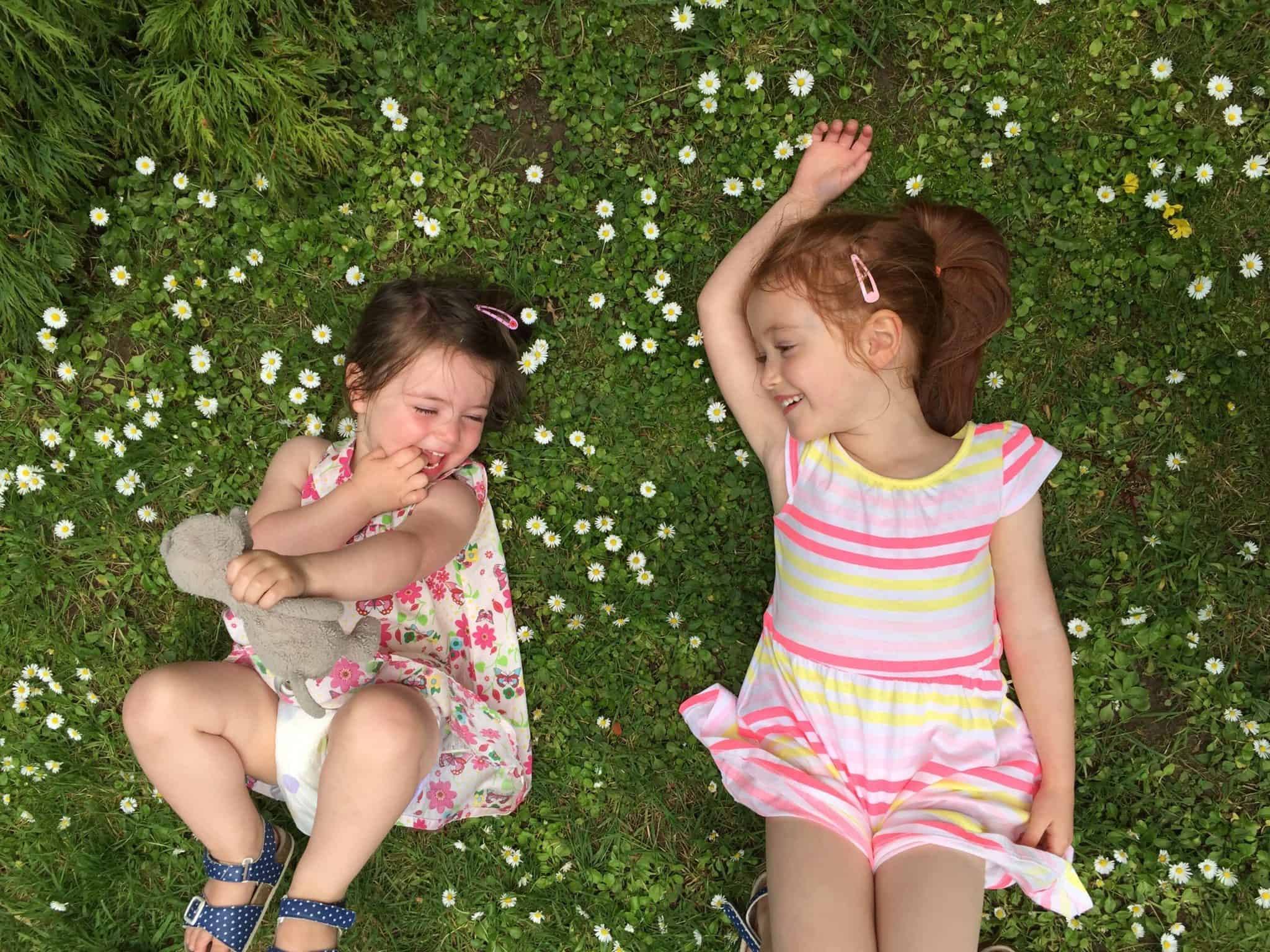 Thea and Ava laughing amongst the daisies