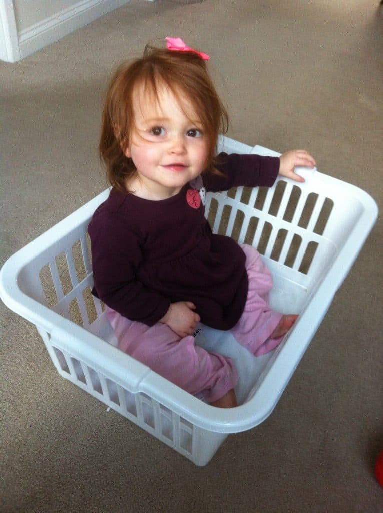 Ava sitting in a washing basket