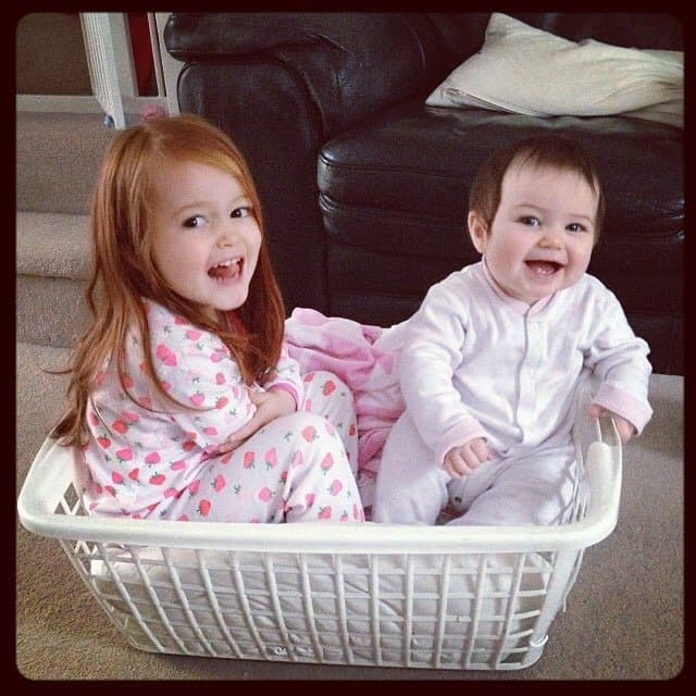 Ava and Thea in a washing basket.