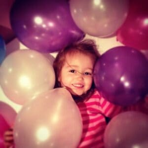 Ava and balloons on her third birthday