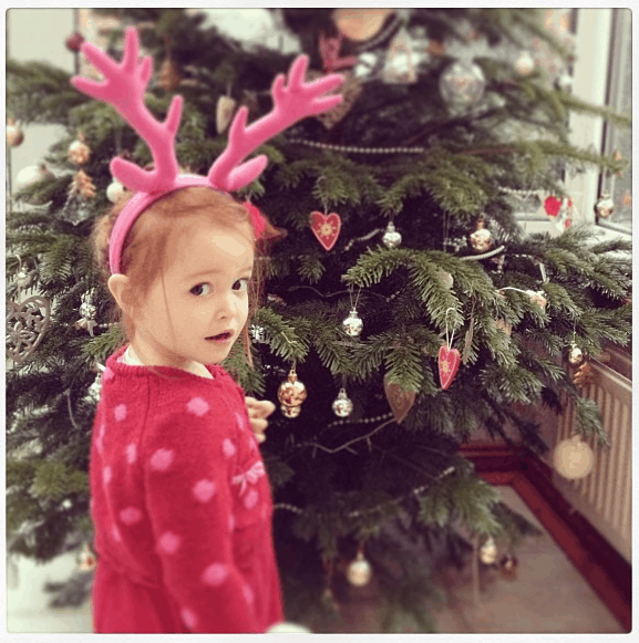 Ava wearing pink antlers by the Christmas Tree