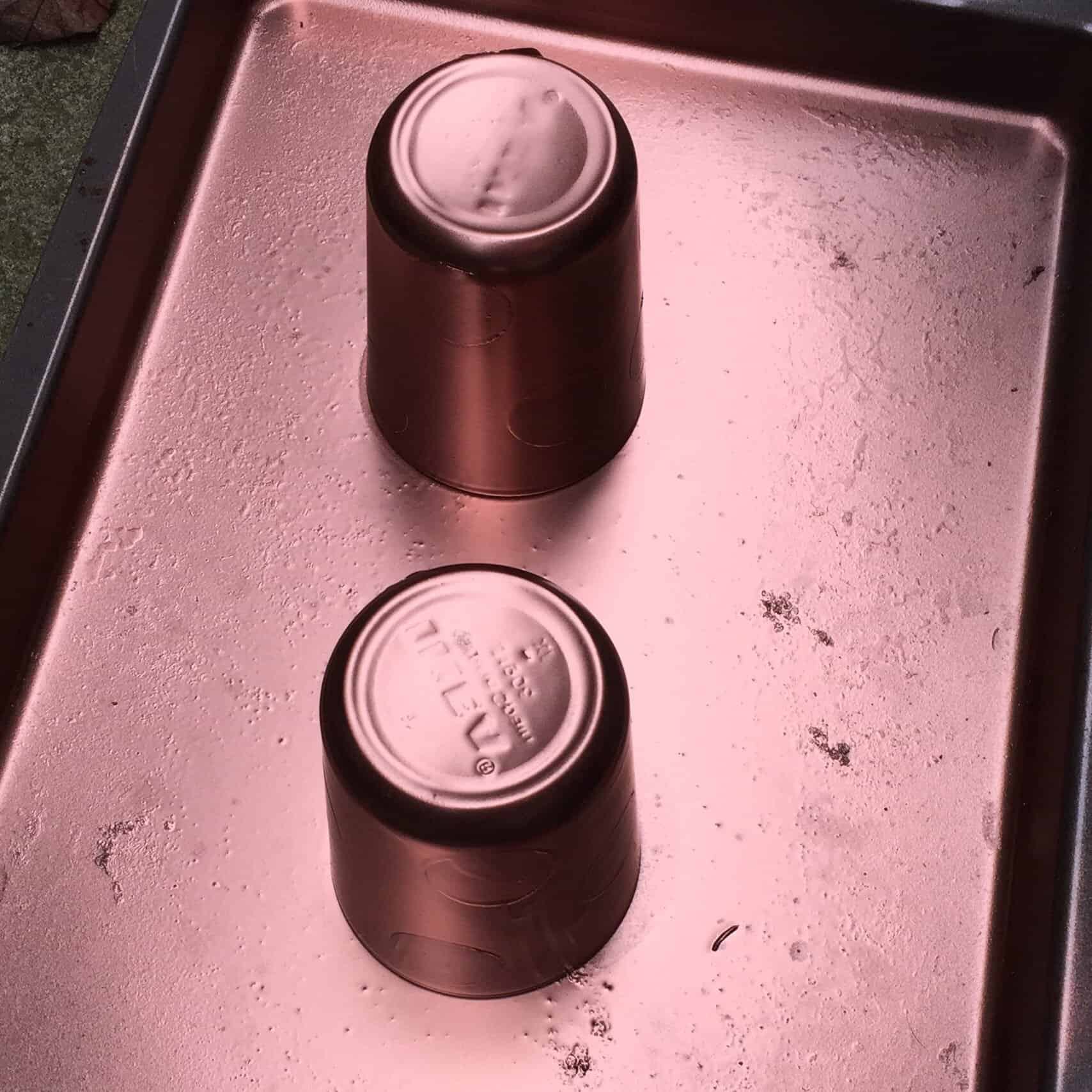 Glasses on a baking tray, sprayed with copper paint.
