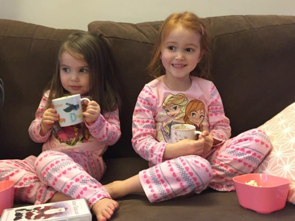 Thea and Ava drinking their hot chocolate and eating popcorn.