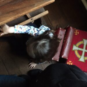 Thea making a fort out of the church kneelers