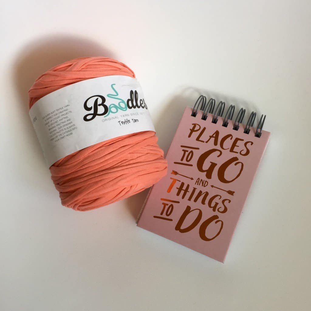 Coral Boodles yarn and pink and copper notebook