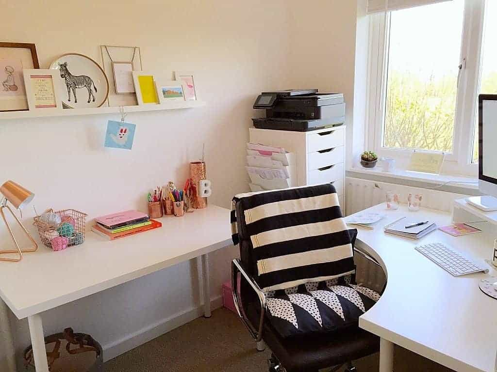 Home office with white IKEA furniture and copper accessories
