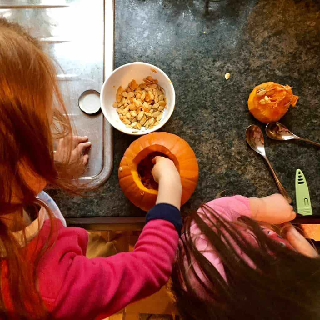Ava and Thea scooping out pumpkins