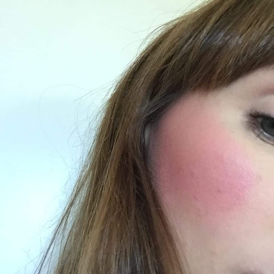 Me wearing PHB Ethical Beauty Pressed Blush brush loaded with Mineral Blusher in Camellia