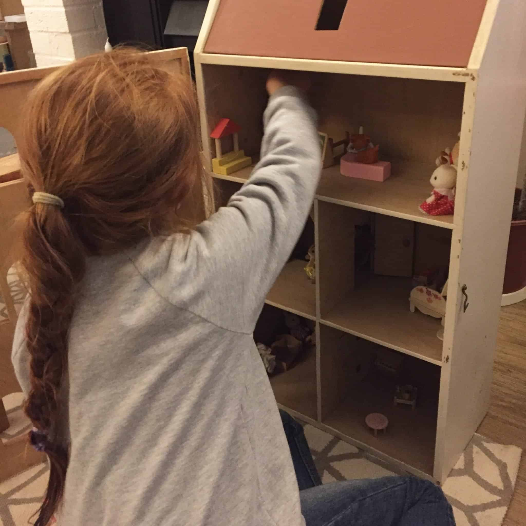 Ava arranging her dolls house