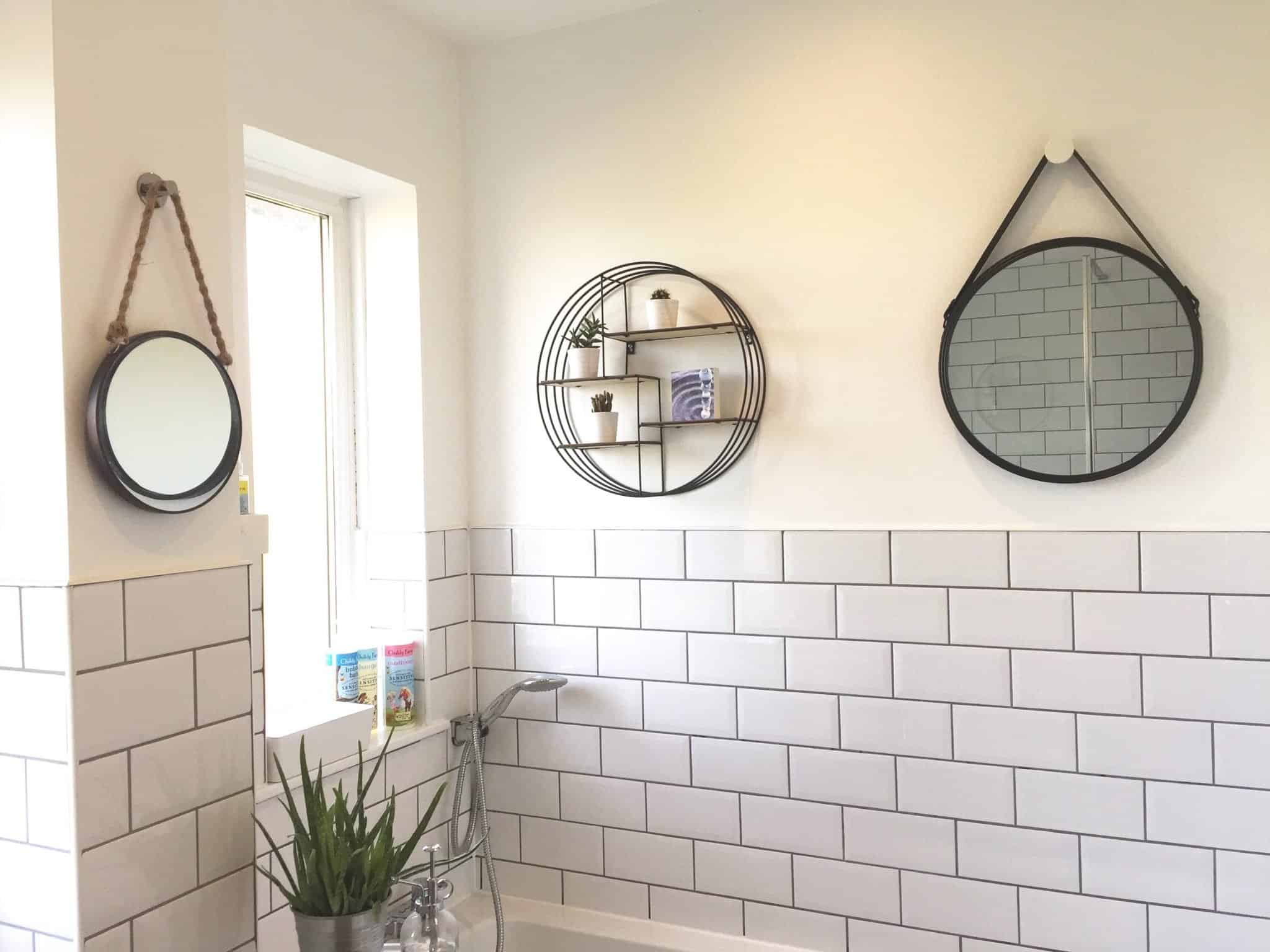 Circular black mirrors and shelving above a bath in a monochrome bathroom