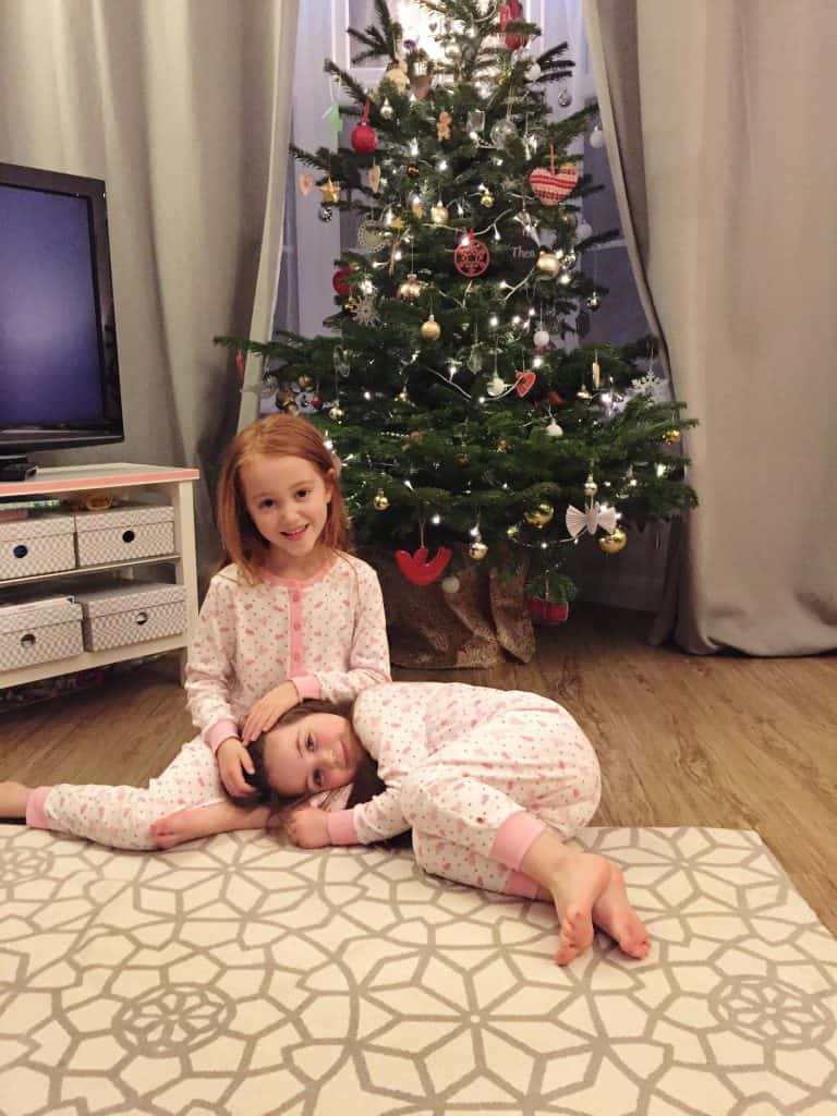 Matching Piccalilly onesies in front of the Christmas tree
