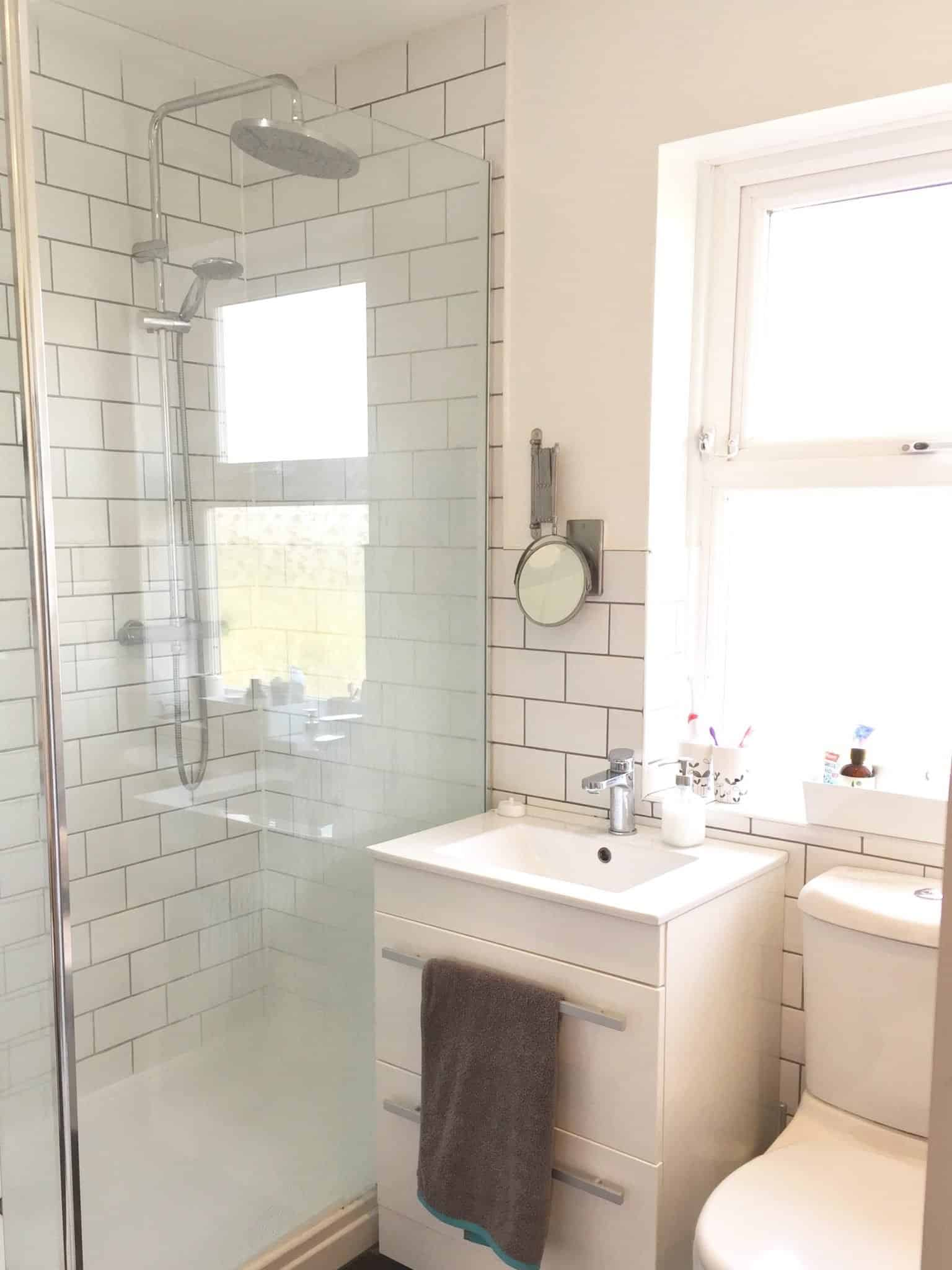 Walk in shower, sink and vanity unit and toilet in monochrome bathroom