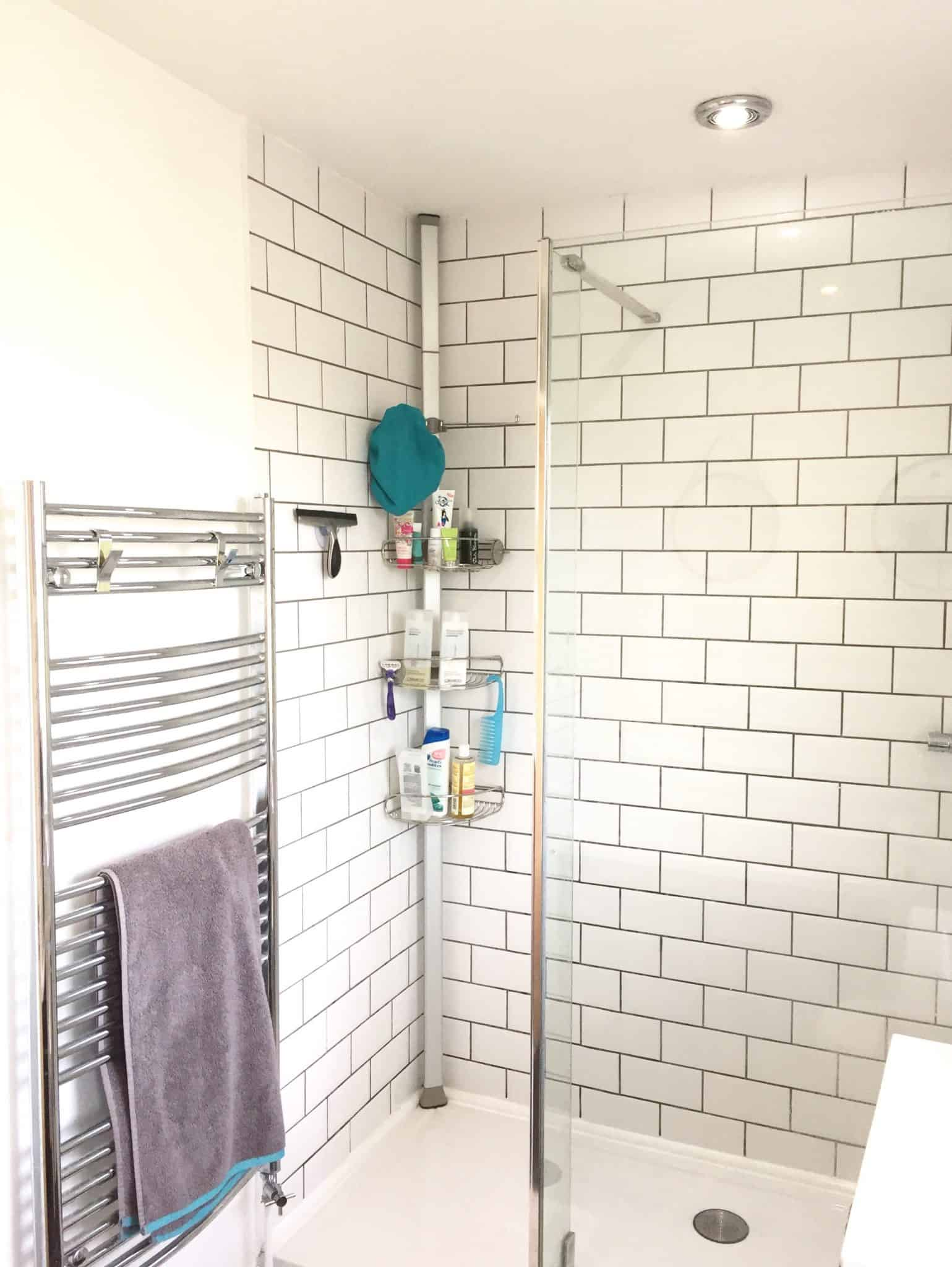 Walk in shower with white metrol tiles and grey grout and SimpleHuman shower caddy