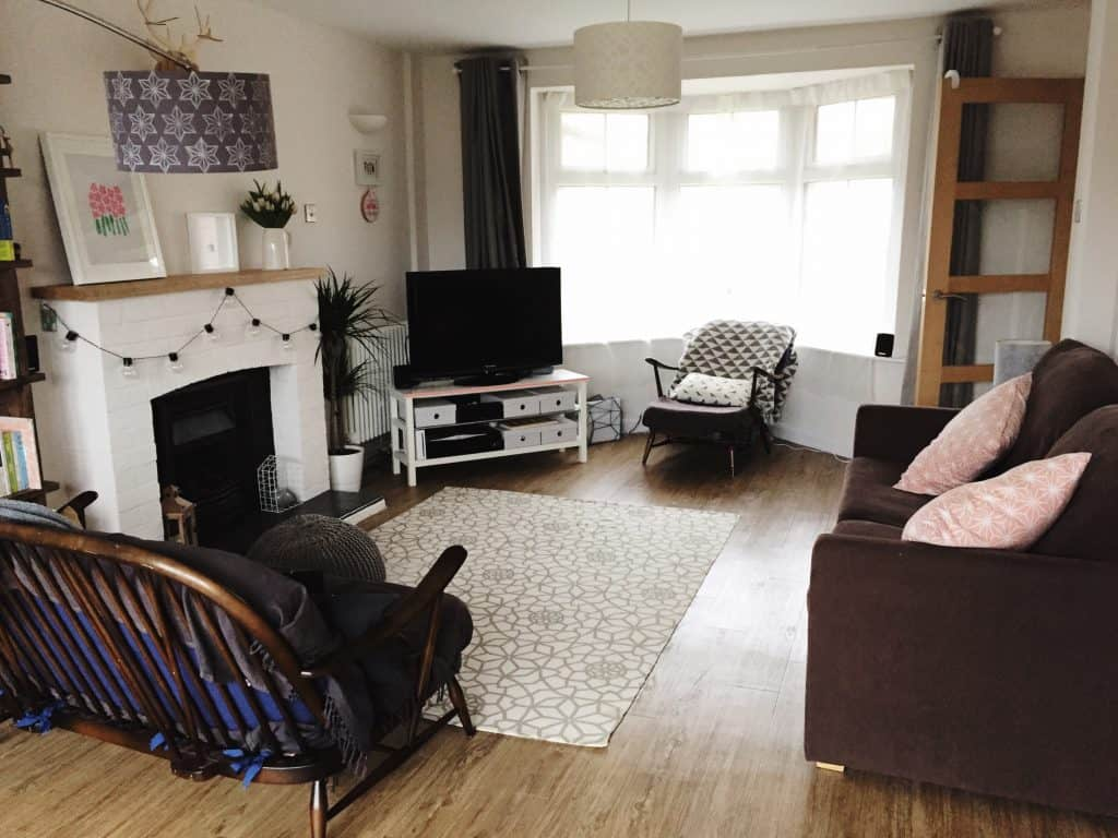 Lounge with bay window, white lasercut lampshades, cool oak floor, white and grey rug, white painted fireplace and Ercol chair