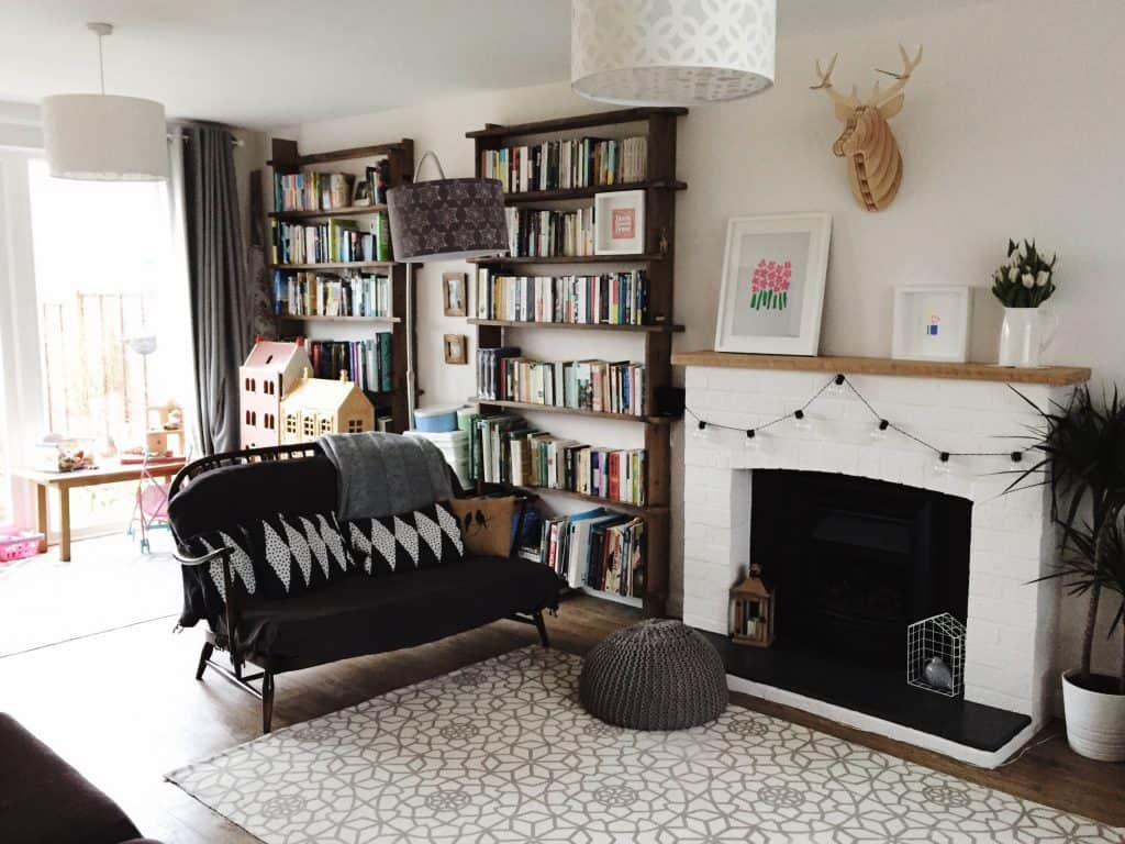 Lounge with handmade open bookshelves, white painted fireplace and Ercol sofa