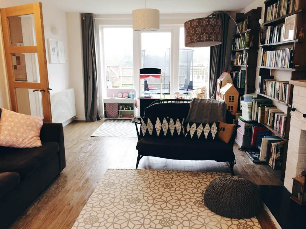 Lounge with patio doors, play kitchen, Ercol sofa adn white and grey rugs on oak floor