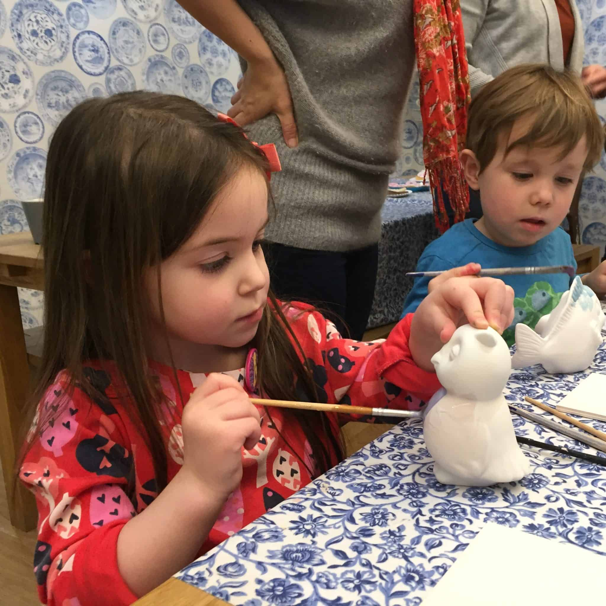 Thea painting her pottery
