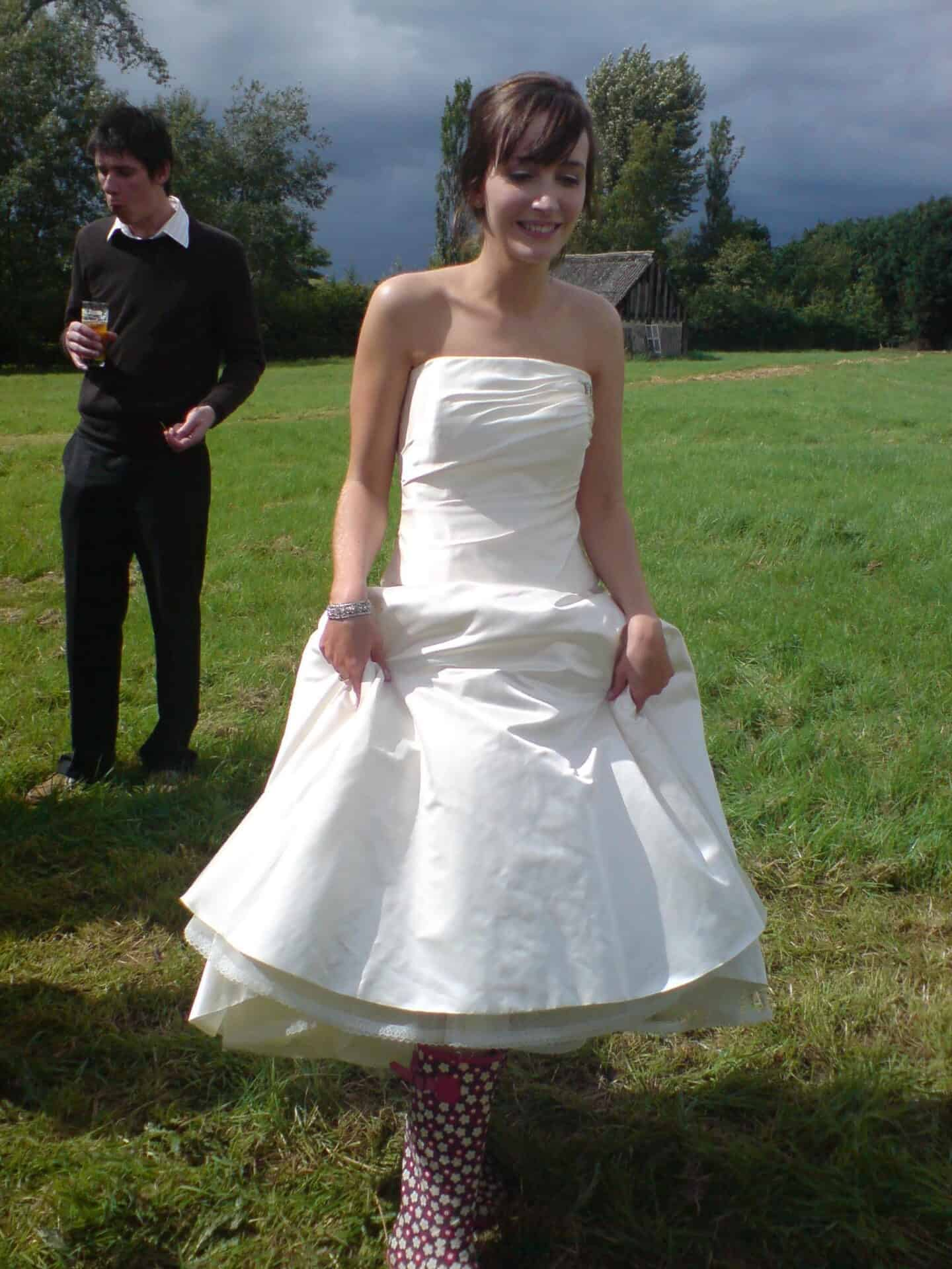 Becky in a wedding dress and wellies
