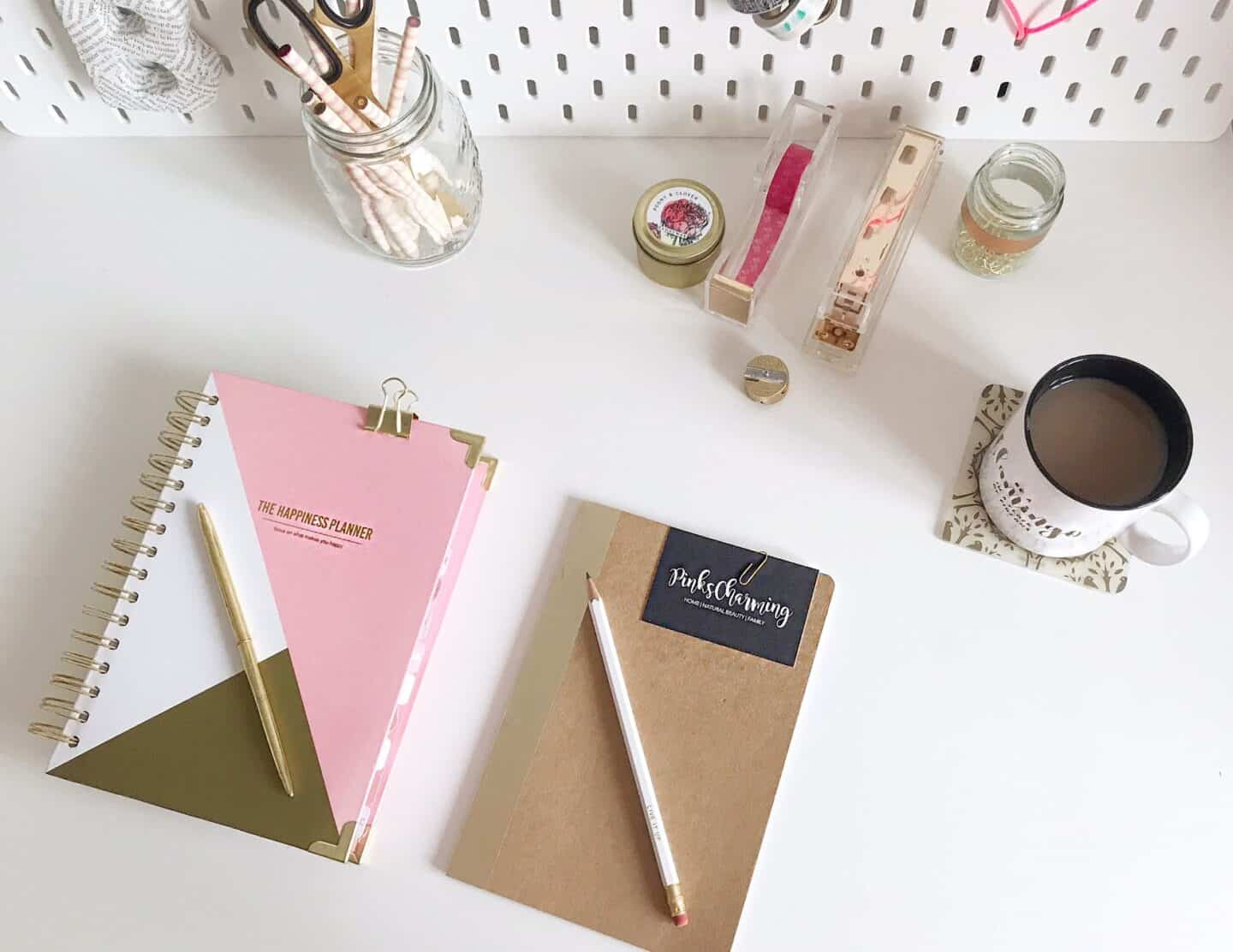 White desk with pink and gold desk accessories and a white peg board