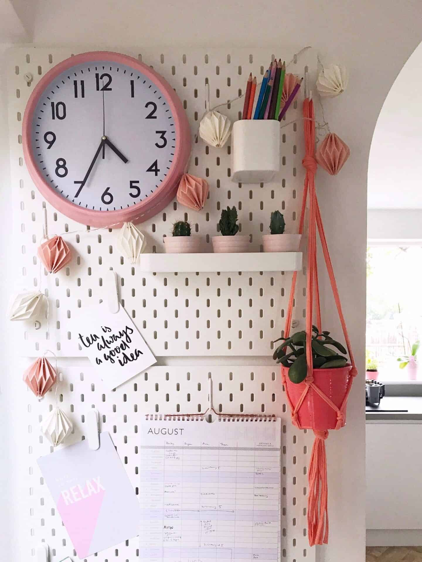 White IEKA Peg Board with Coral Pink Macrame Plant Hanger