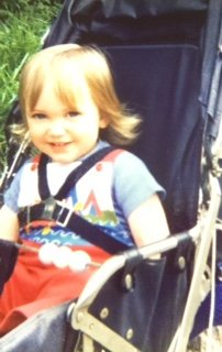 Becky in a push chair in dungarees
