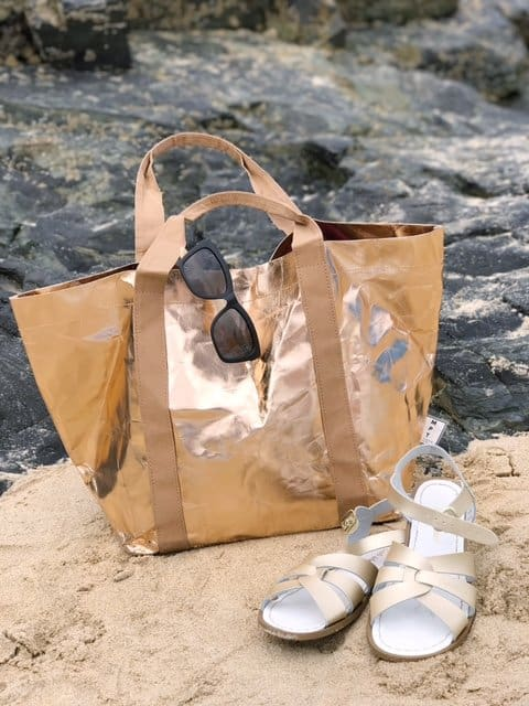 Sustainable tote bag by My Paper Tote on a beach with Sun Salt-Water Sandals