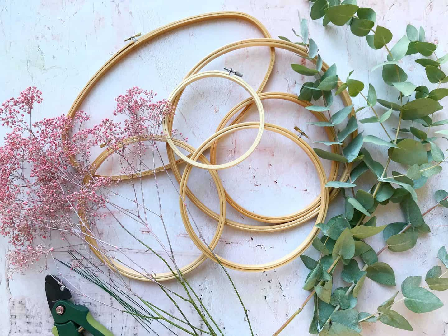 Materials to make winter wreaths with emboridery hoops and foliage