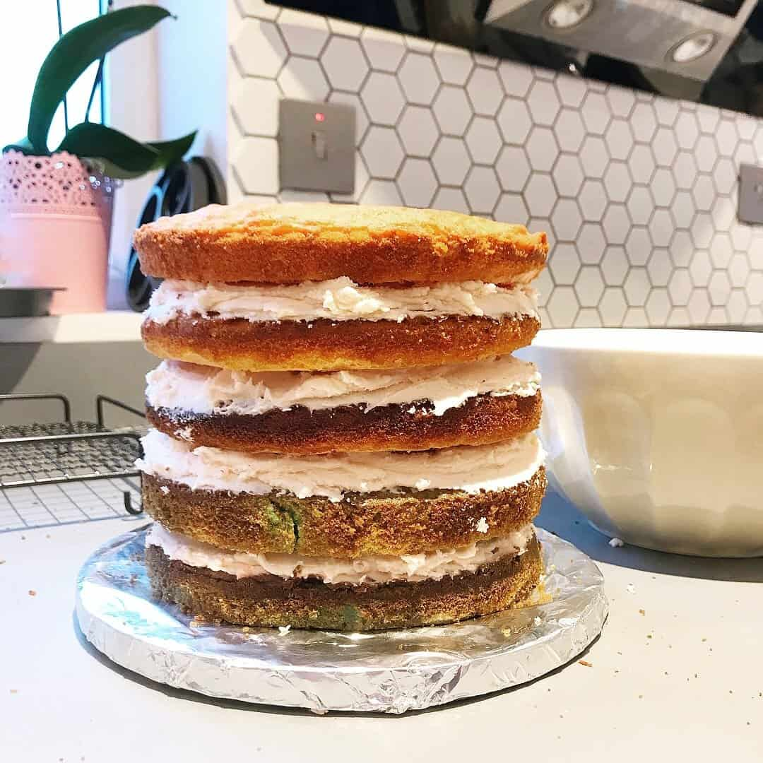 The stack of rainbow cakes, sandwiched together with butter icing