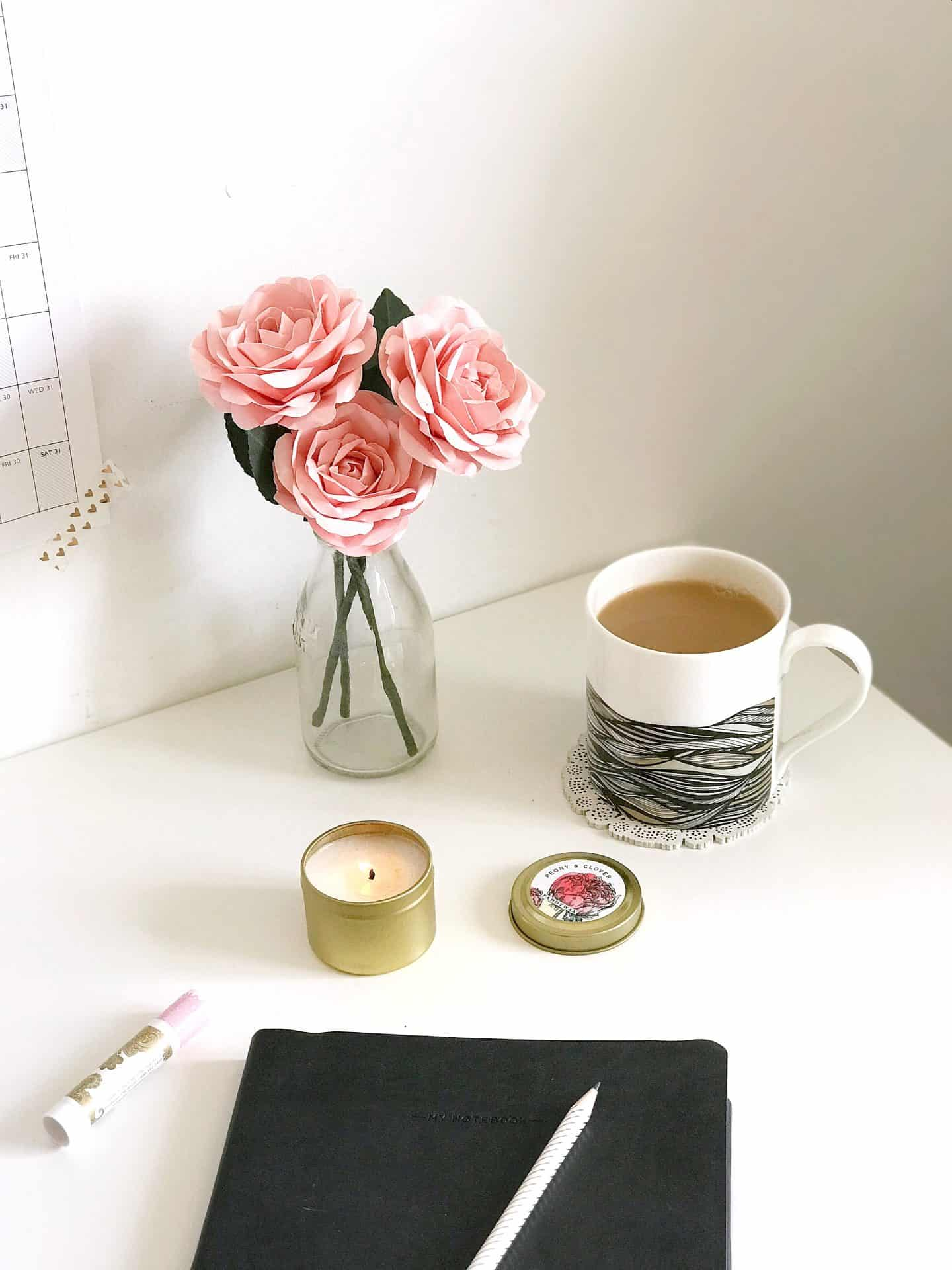 Black notebook, pink roses, candle and black and white mug