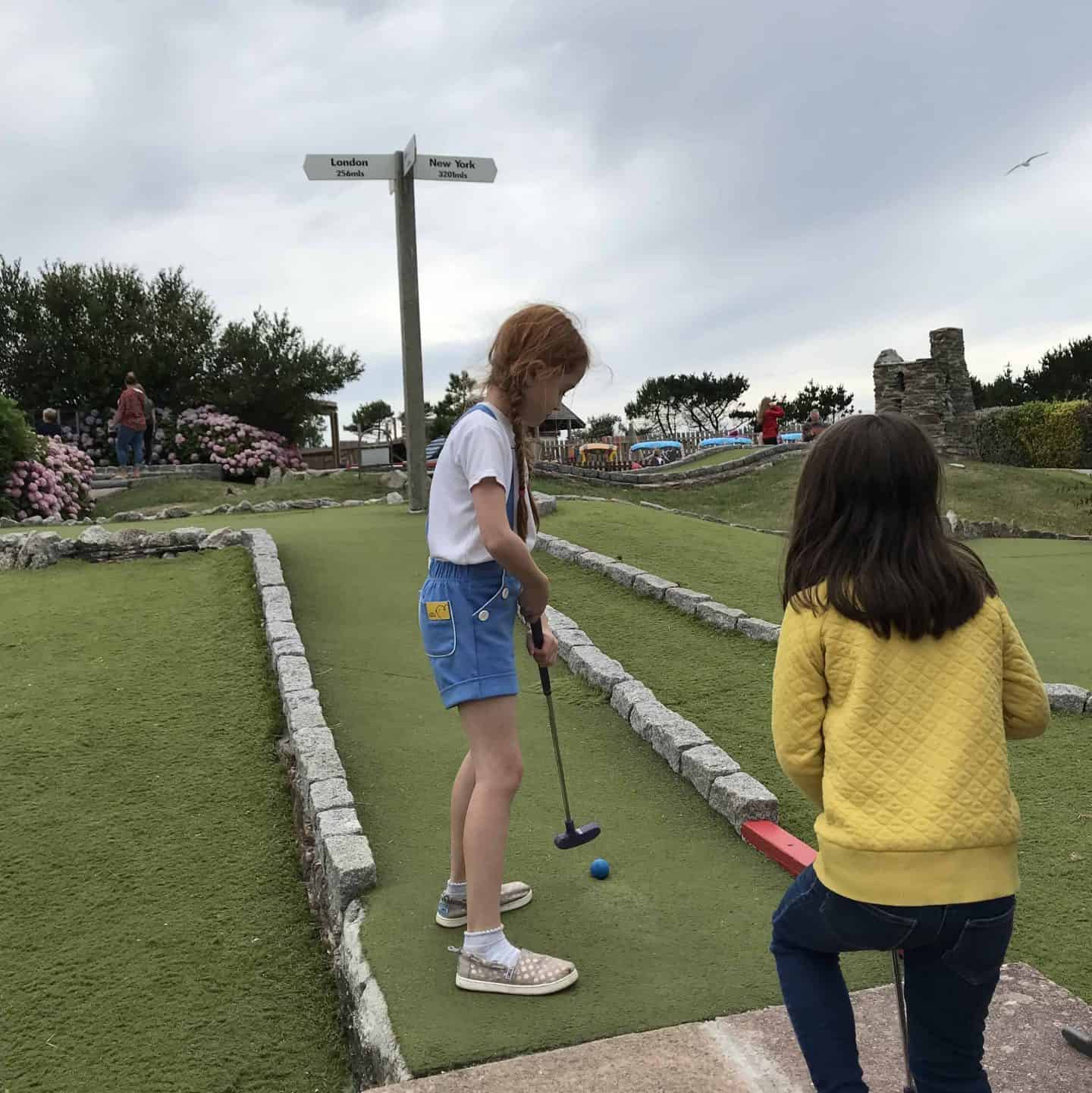 Kids playing crazy golf at Holywell Bay Fun Park, Cornwall