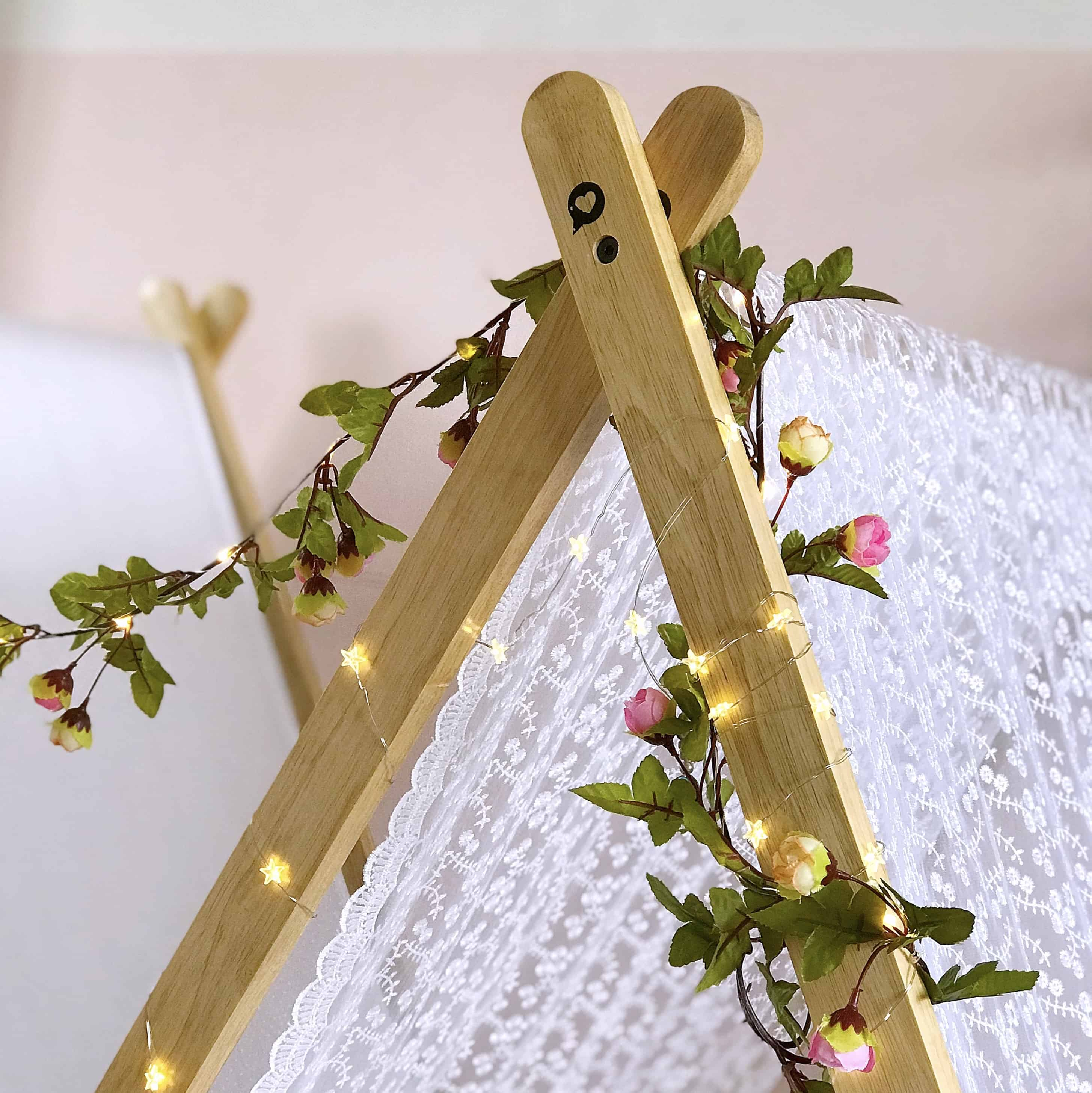 Star fairy lights and light up floral garland on a kids indoor tent
