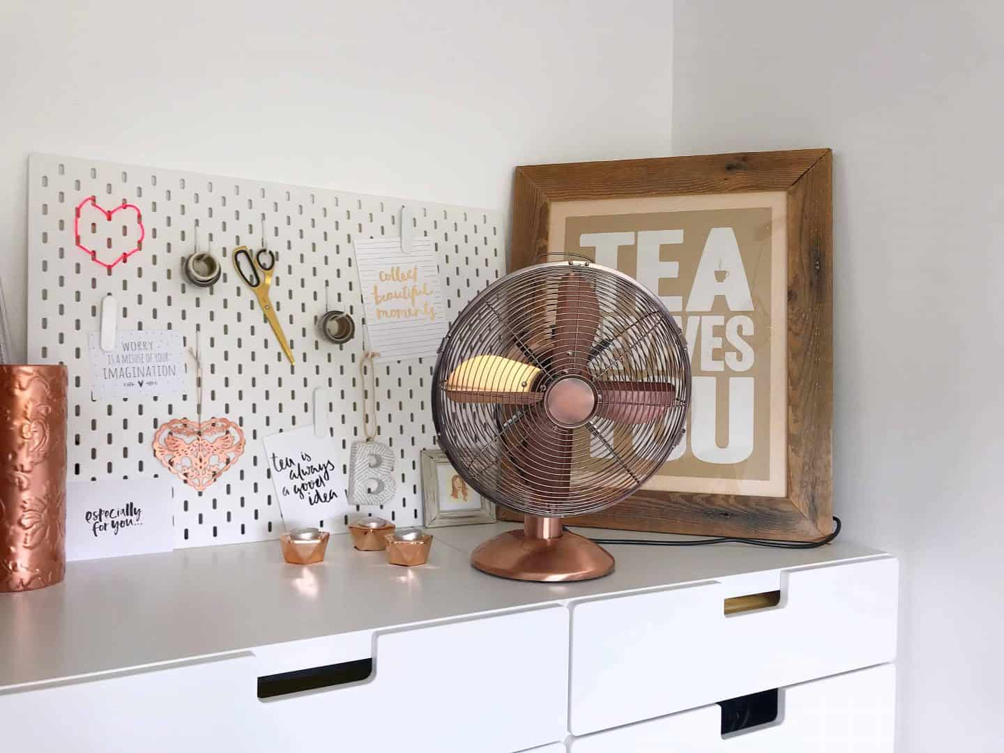 White IKEA pegboad, vintage style copper fan and white storage