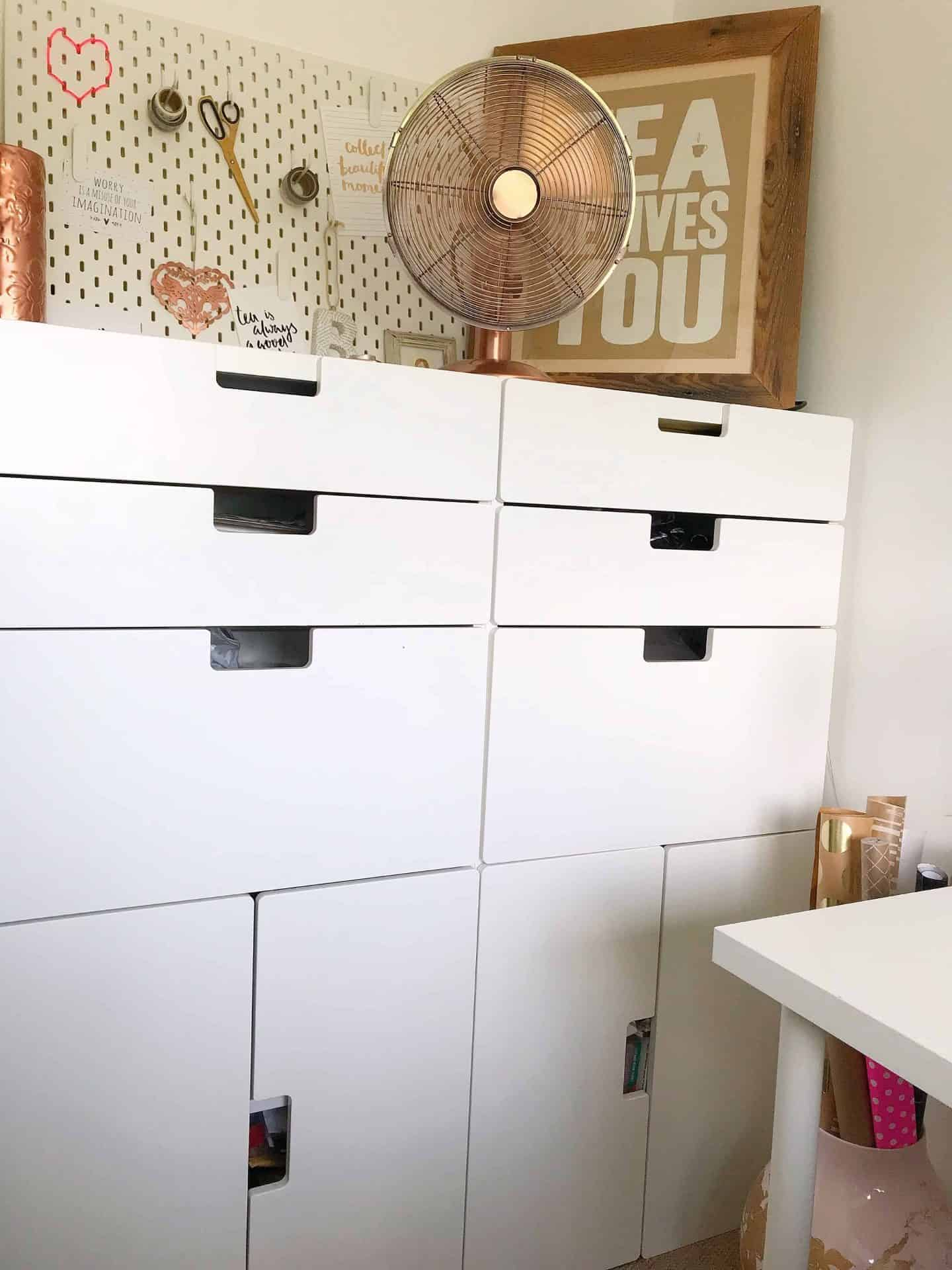 White IKEA storage cupboards with desk fan and peg board
