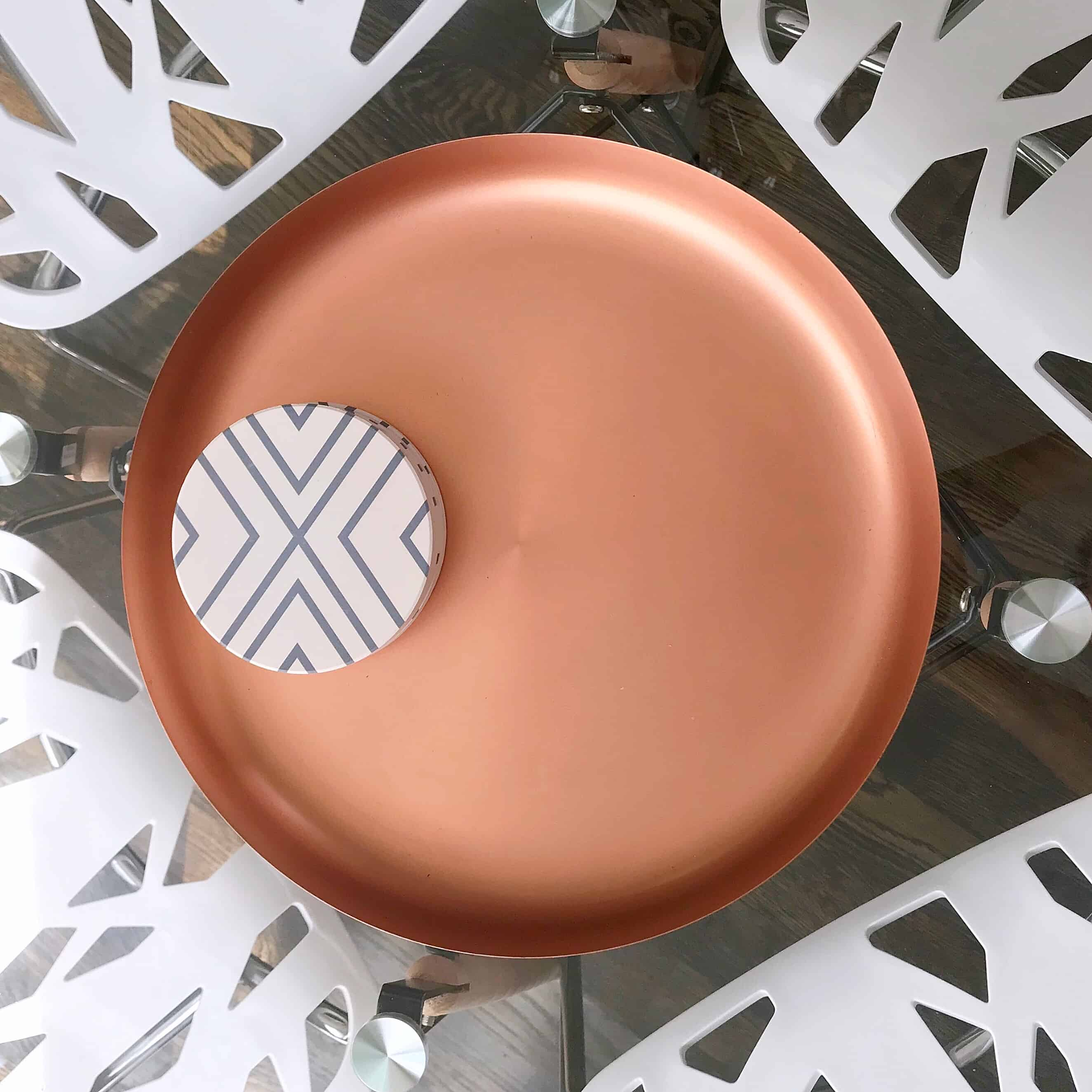 Glass table with copper tray and white chairs below