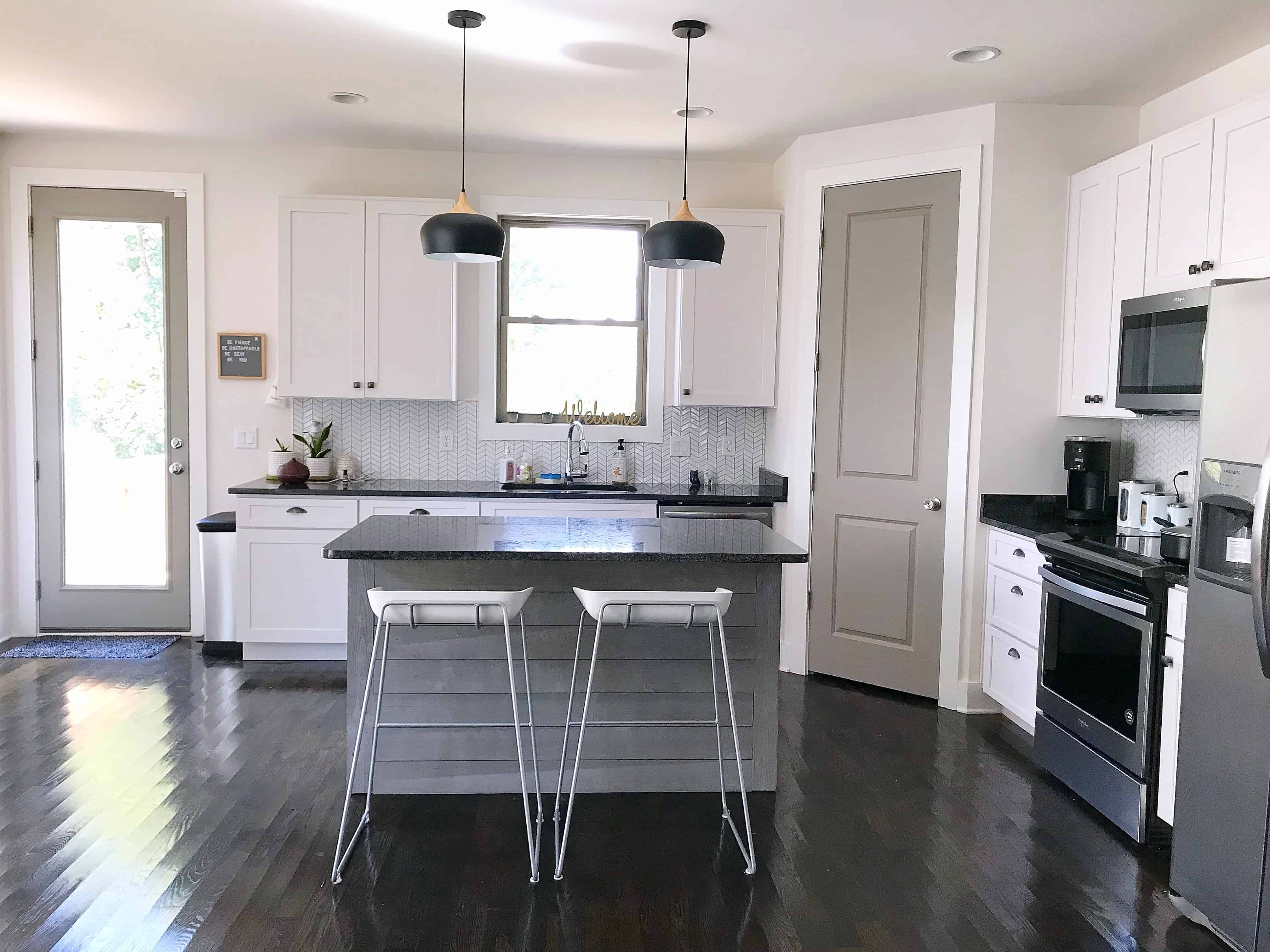 Monochrome kitchen with island and bar stools