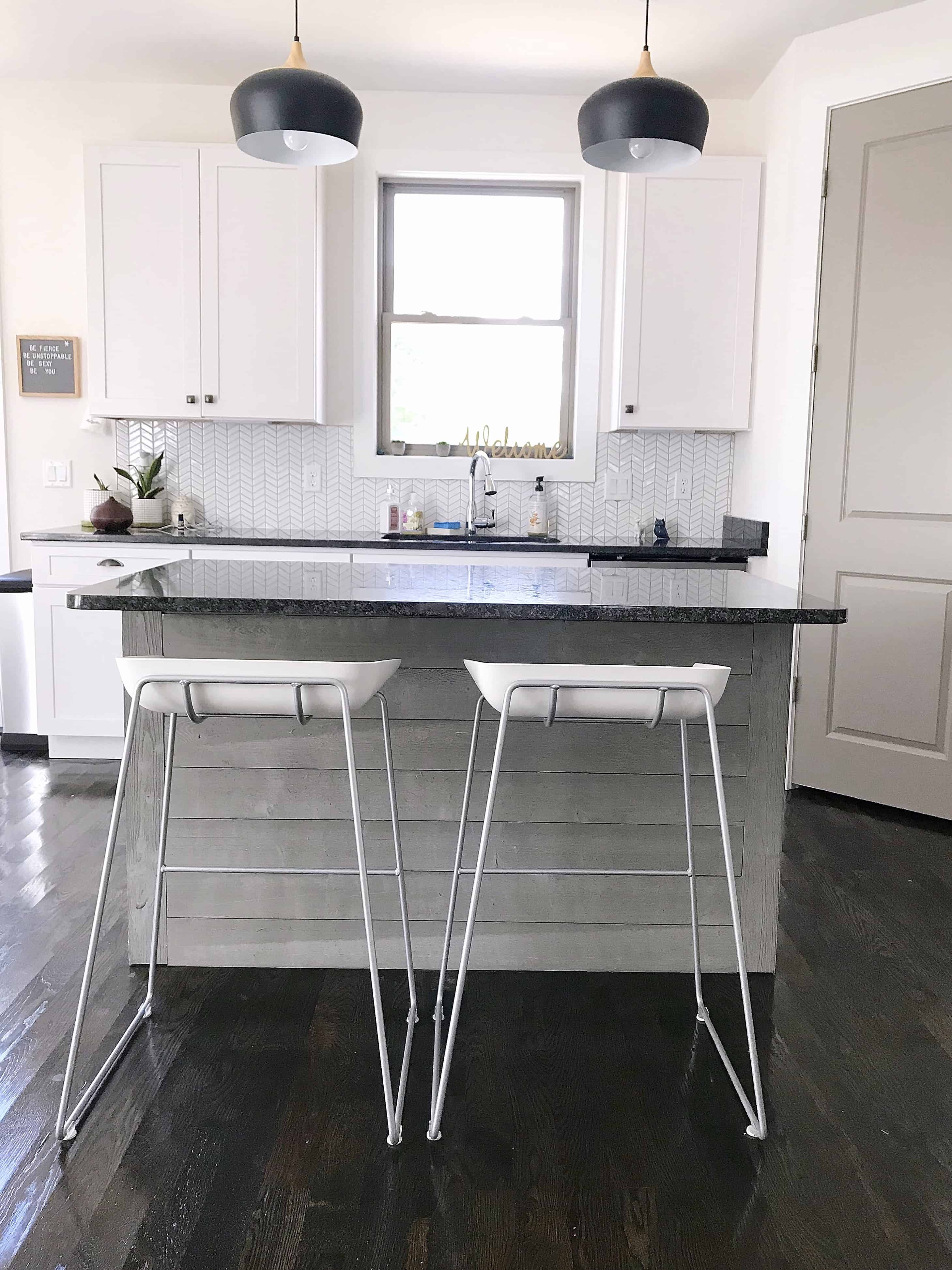 White and black kitchen with island and bar stools