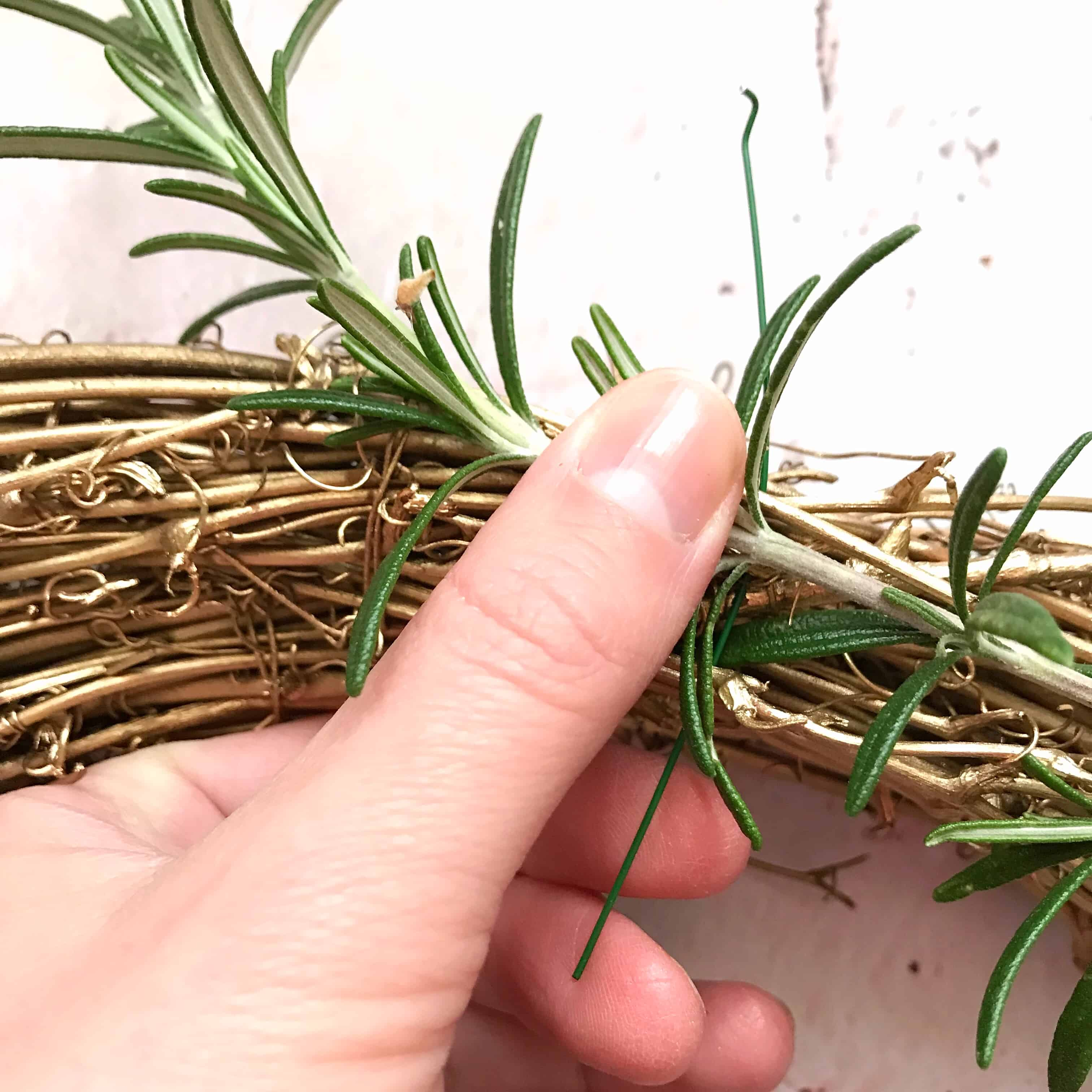 Attach greenery to autumn wreath using floristry wireAttach greenery to autumn wreath using floristry wire
