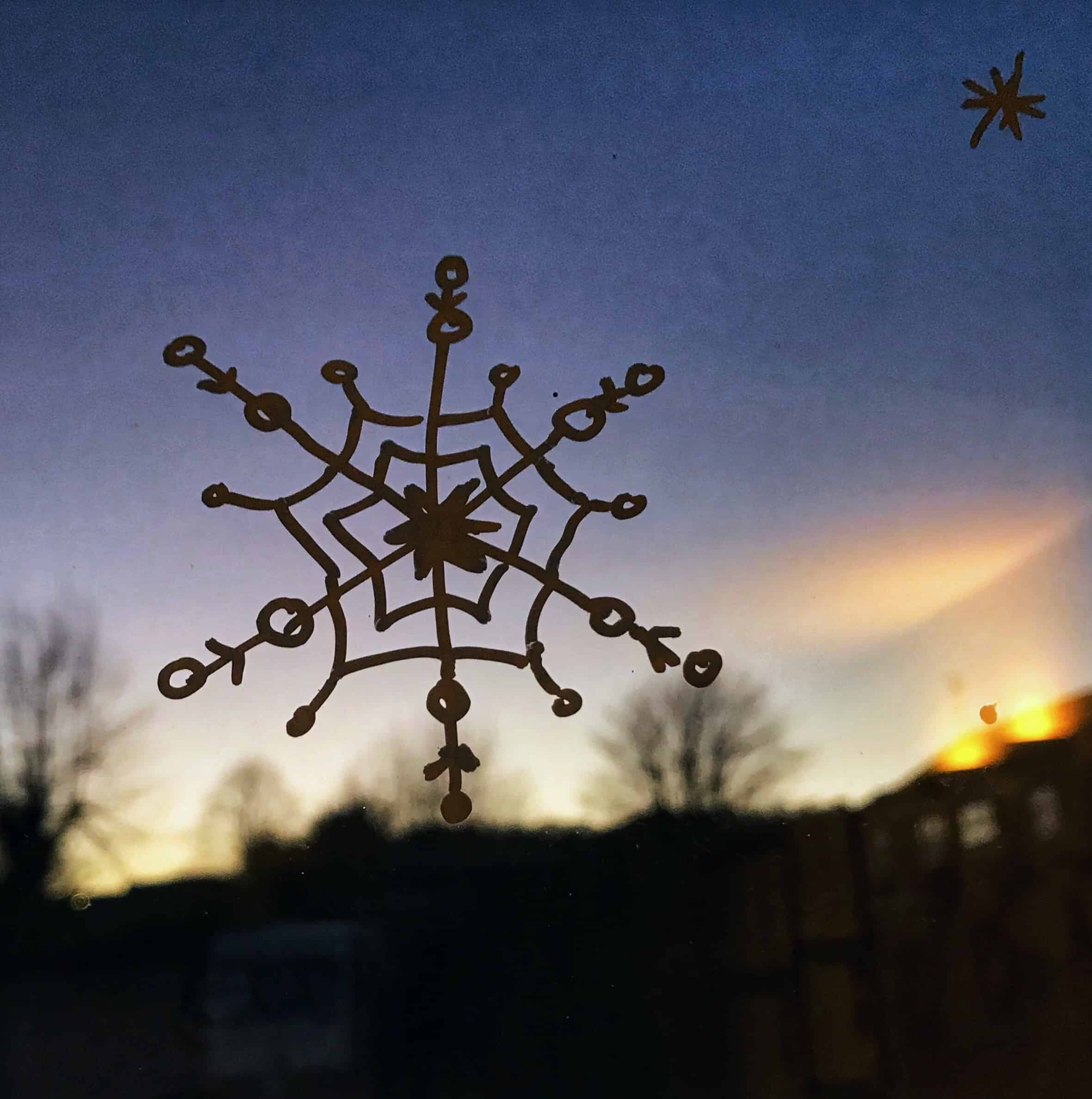 Chalk pen snowflake on a window