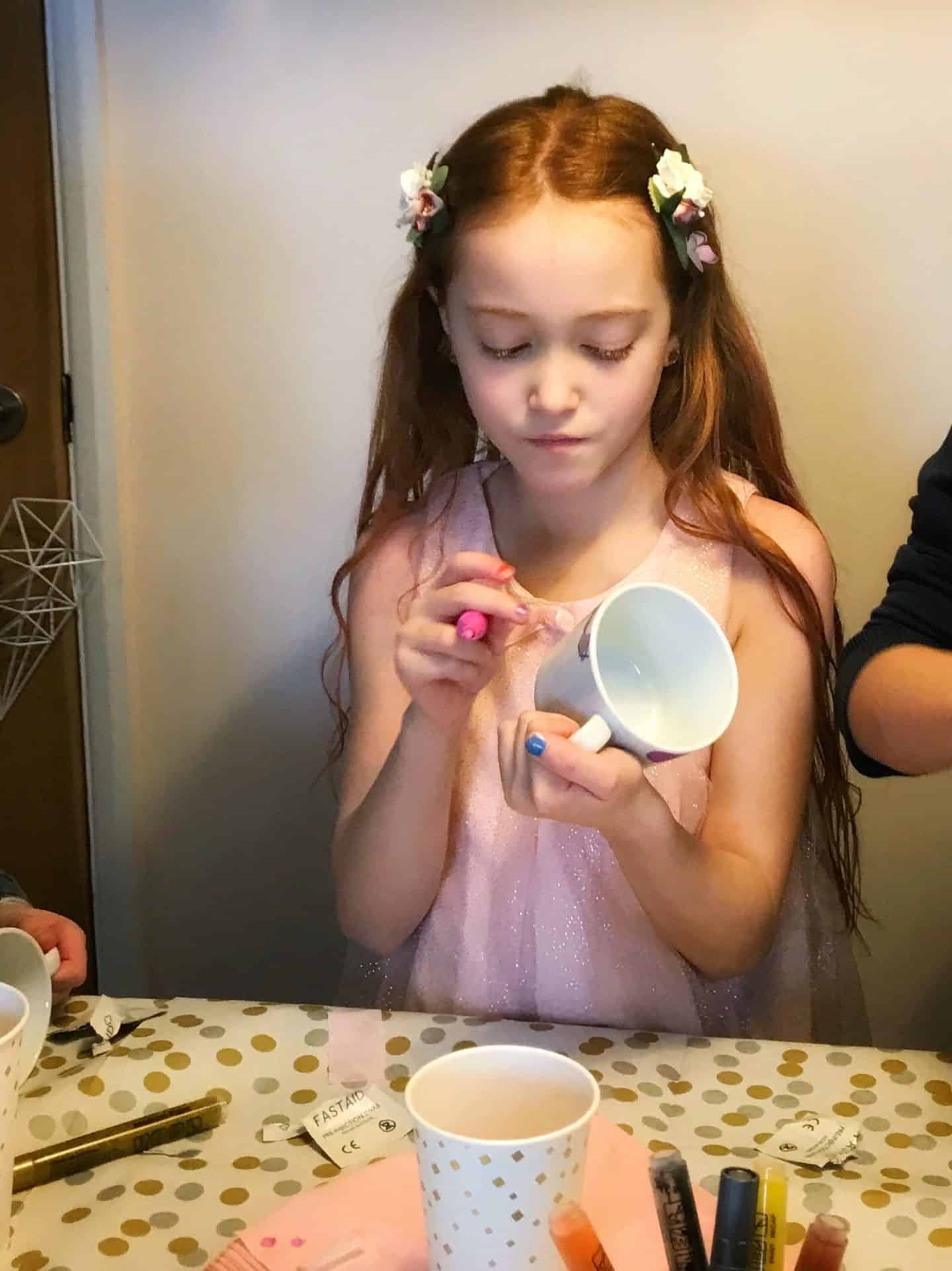 The birthday girl decorating a mug with ceramic markers