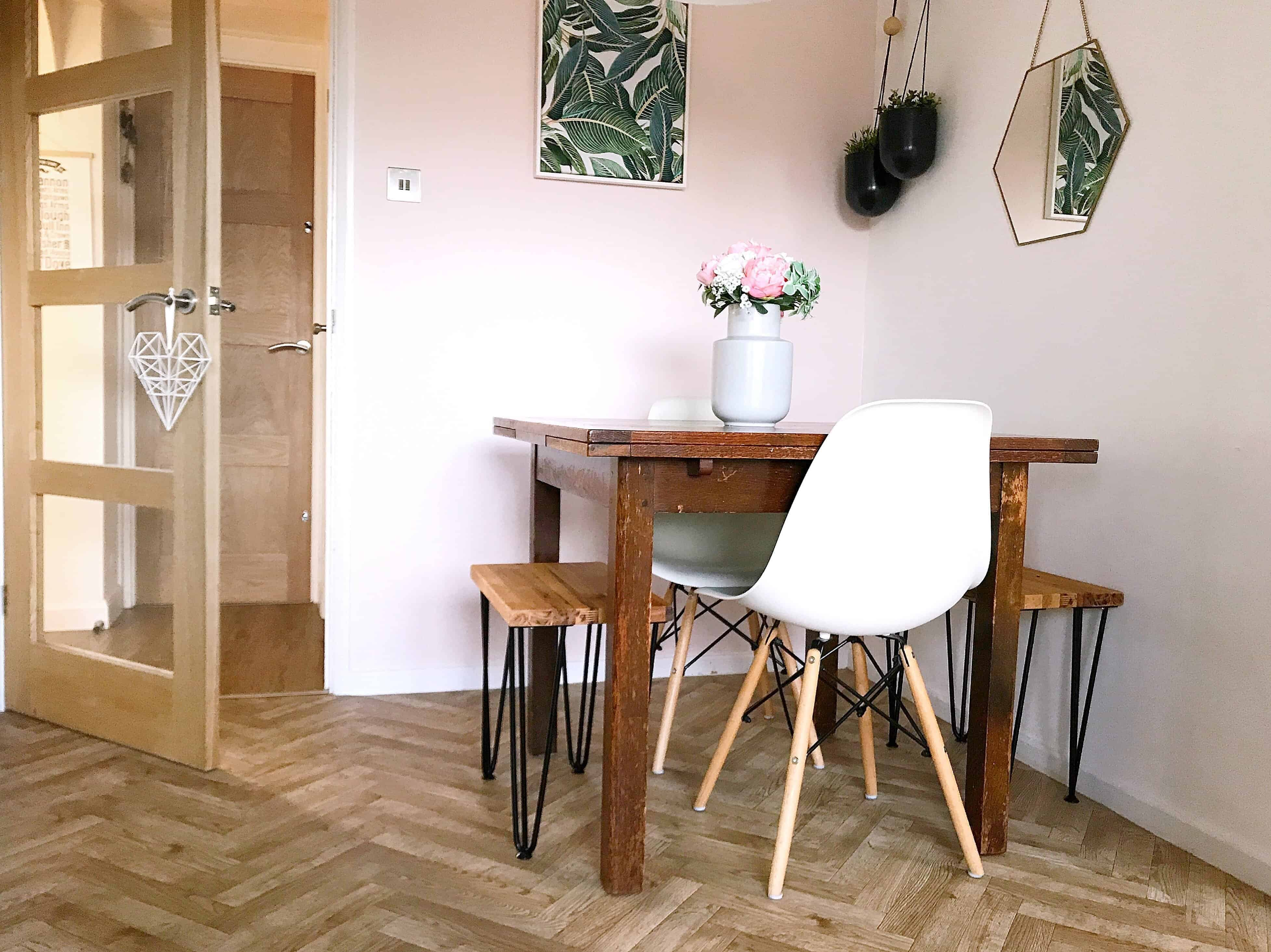 Dining room with herringbone floor, table with white chairs, stools and a hexagon mirror