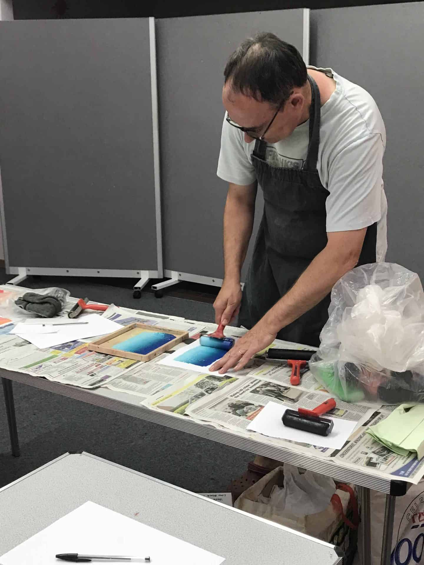 The artist demonstrating printing at MK Library