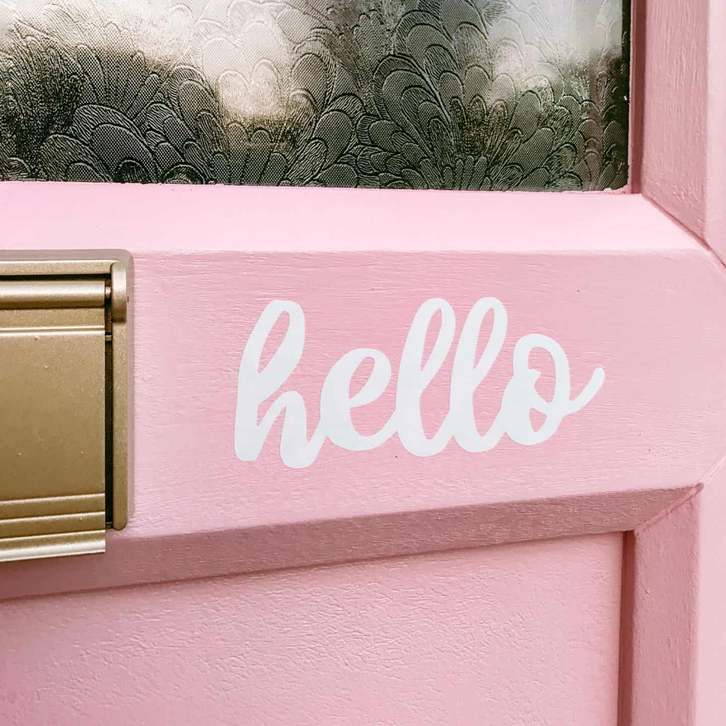 Hello vinyl sticker on a pink painted uPVC front door next to a gold letterbox