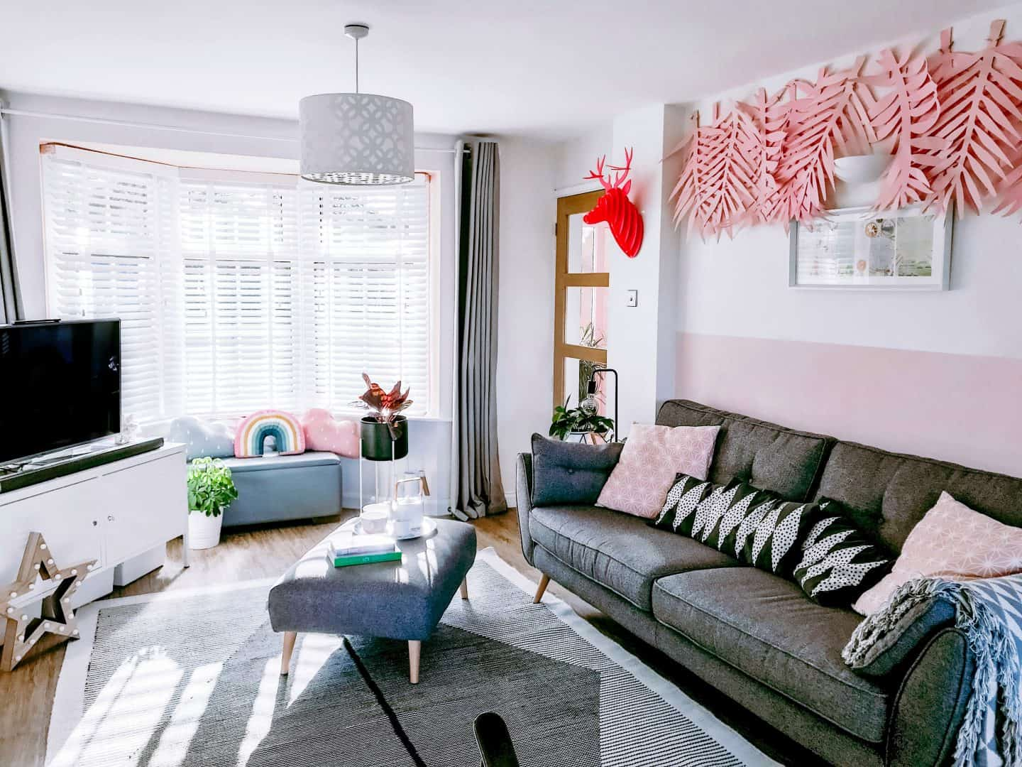 Monochrome lounge with pink acccents and white wooden blinds with tapes
