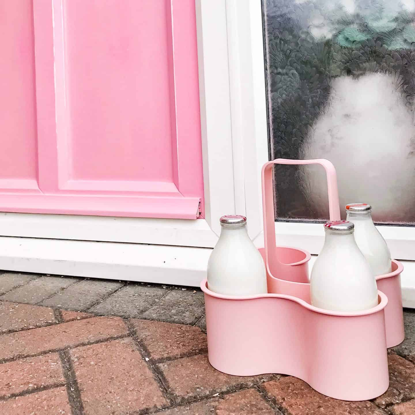 Pink milk minder with milk bottles in front of a pink painted front door
