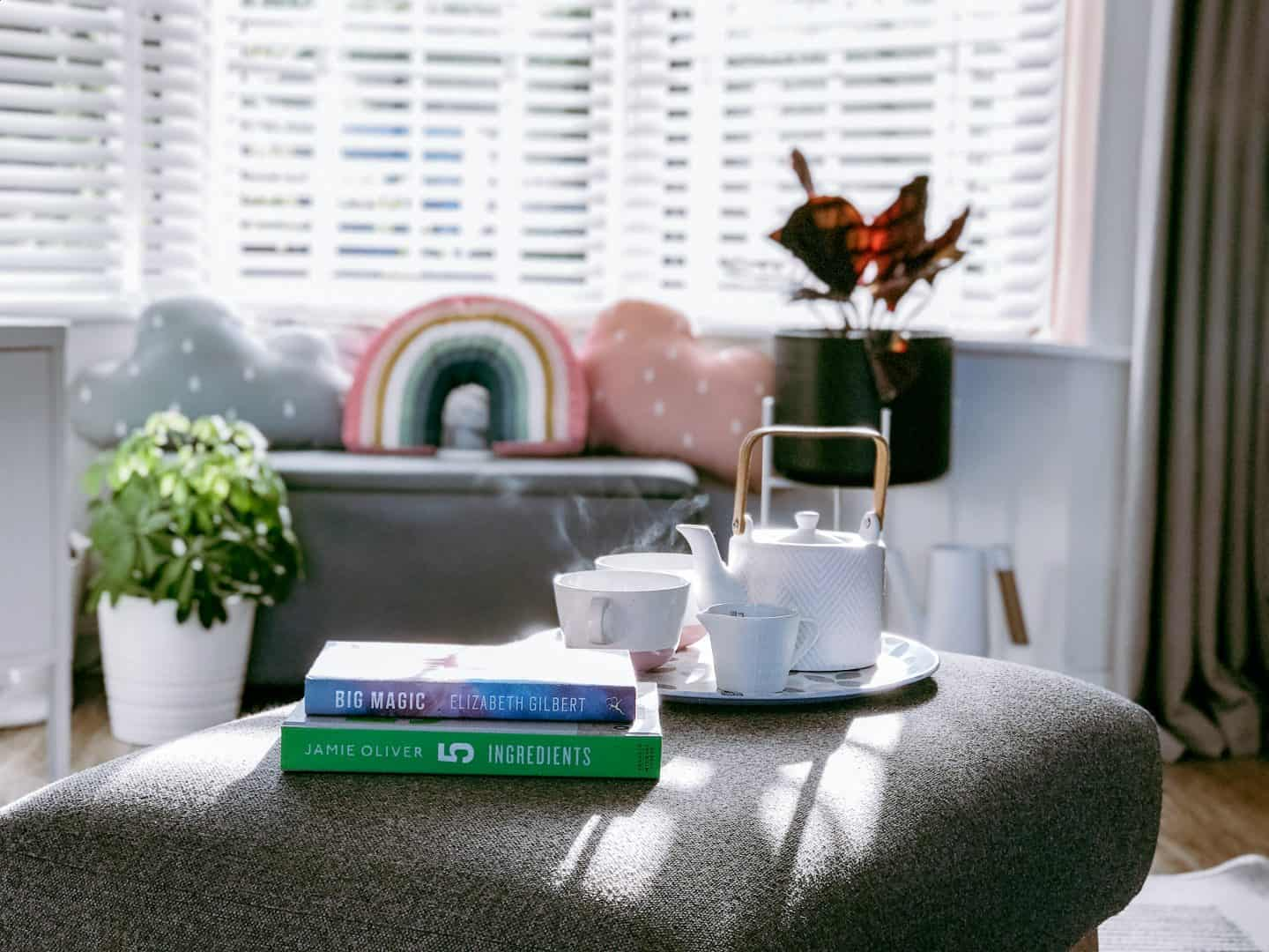 Tea tray and books in front of white wooden blinds with tapes