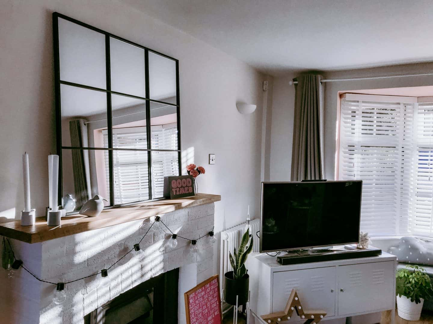 White lounge with black, white and pink features with a wooden blind reflected in an industrial mirror