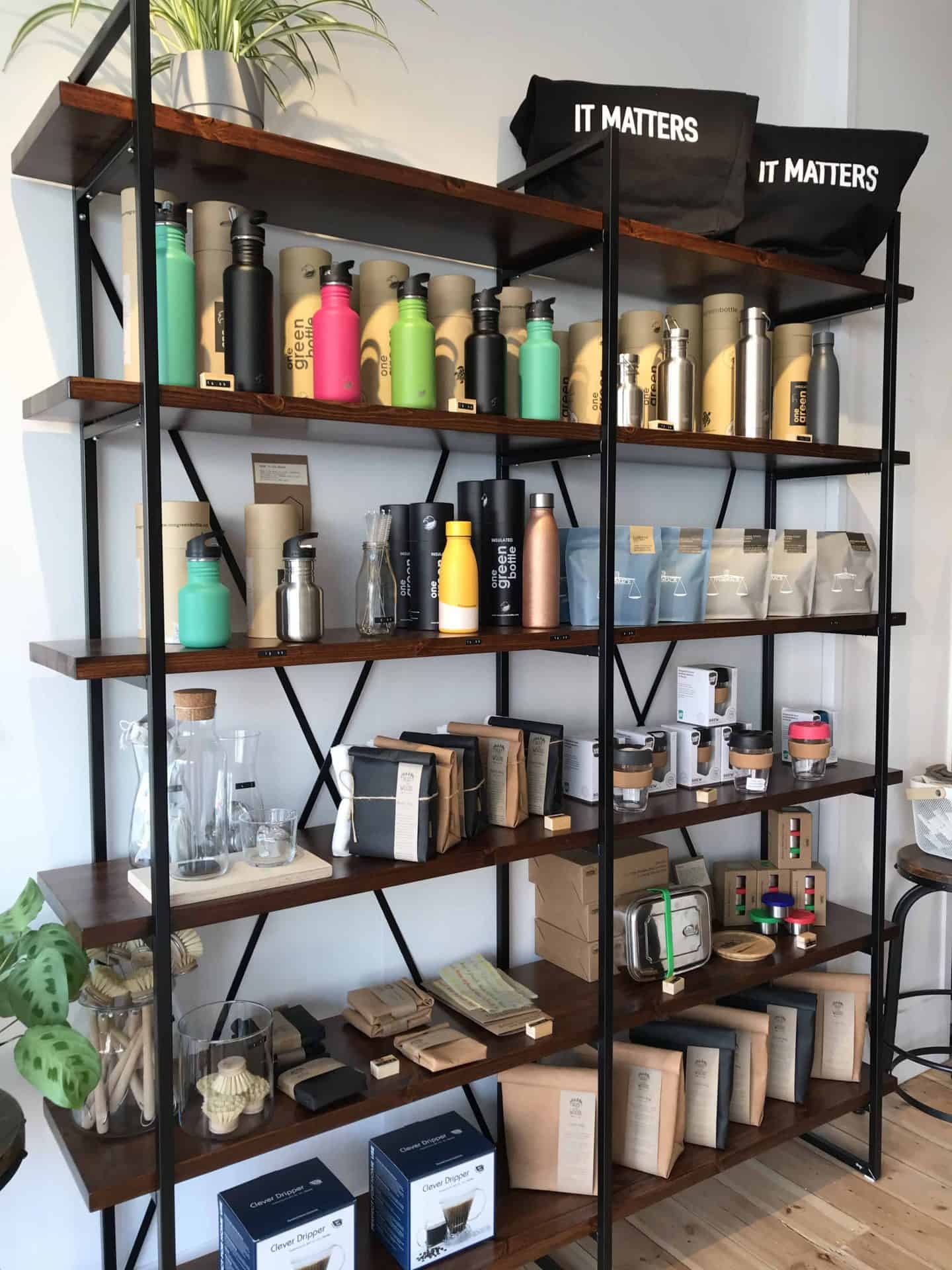 Reusable water bottles and bags, and other eco-friendly products on shelves at Barnes + Binns in Hove