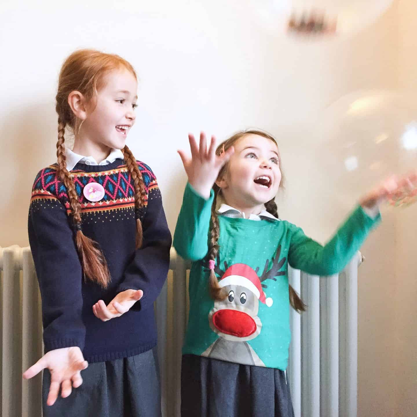Two girls wearing Christmas jumpers playing with balloons