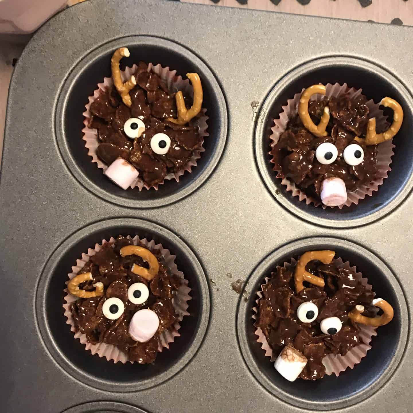 Decorate your chocolate conflake cakes with broken pretzels, candy eyes and marshmallows to make reindeer faces